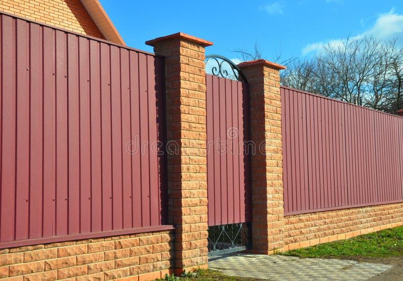 Barrière de brique et en métal avec la porte et la porte Clôture de la construction image stock