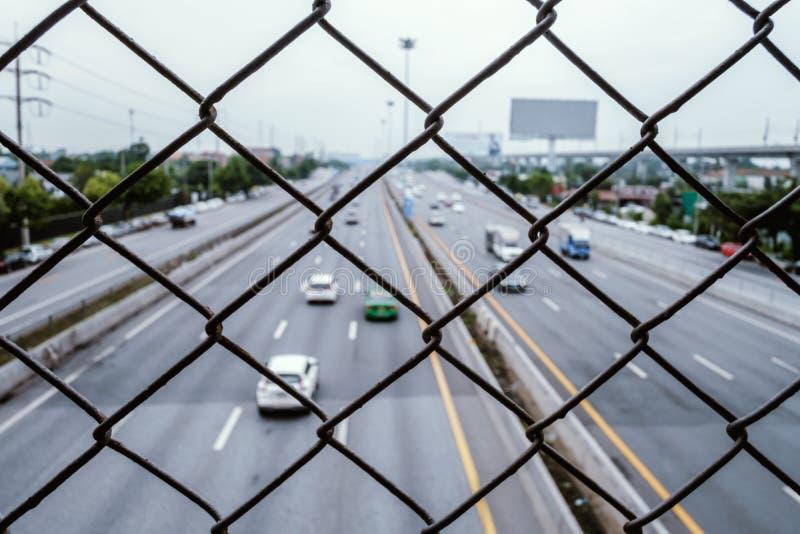 Barrière de grillage avec le fond d'autoroute photographie stock libre de droits