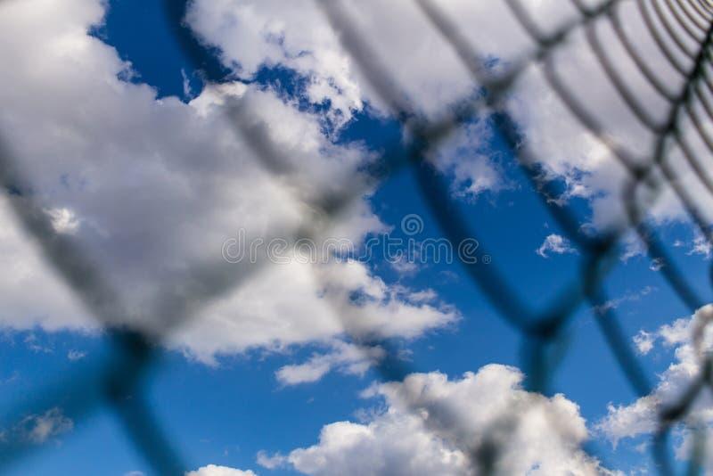 Barrière de maille en métal de Rabitz sur le fond de ciel bleu photographie stock