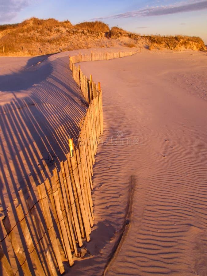 Barrière de plage sur des dunes au coucher du soleil photos stock