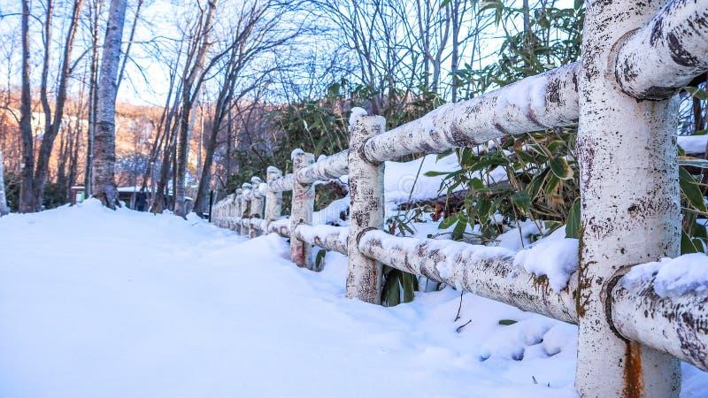 Barrière en bois avec la chute de neige importante image stock
