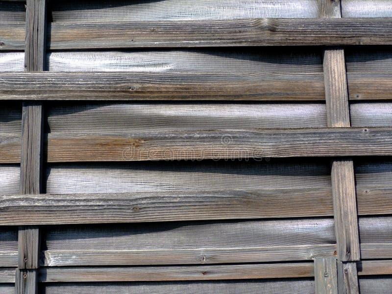 barrière en bois coudée tissée mince de lamelle des bandes horizontales sur le cadre vertical avec le remplissage de vinyle images libres de droits