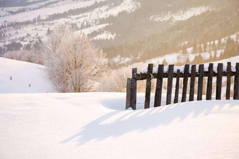 Barrière en bois dans la neige et la lumière du soleil de matin photo stock