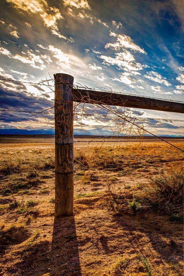 Barrière en bois de barbelé de courrier sur la prairie photographie stock libre de droits