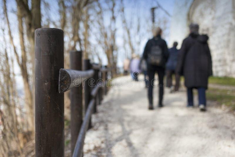 Barrière en bois et beaucoup de marcheurs images stock