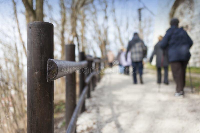 Barrière en bois et beaucoup de marcheurs photo stock