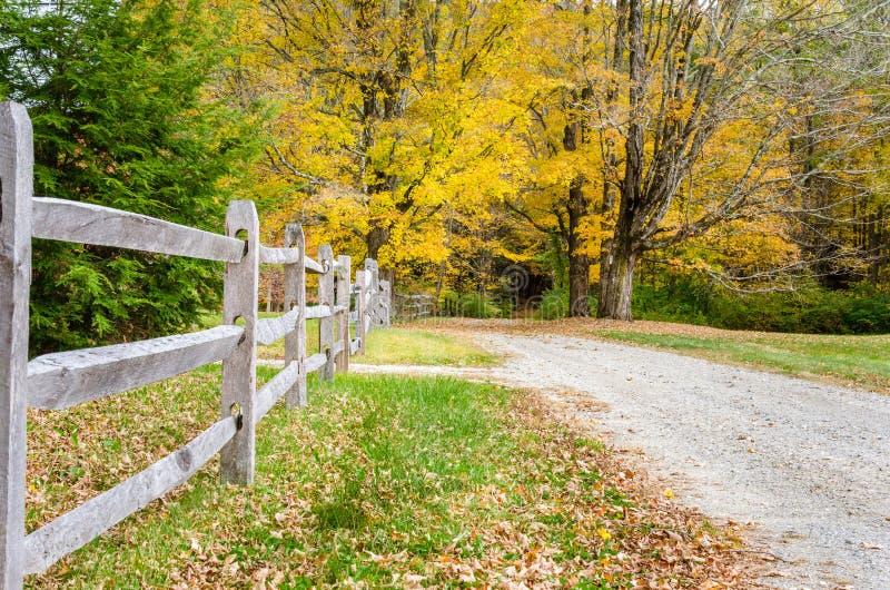 Barrière en bois le long d'une route de gravier aux bois photographie stock libre de droits