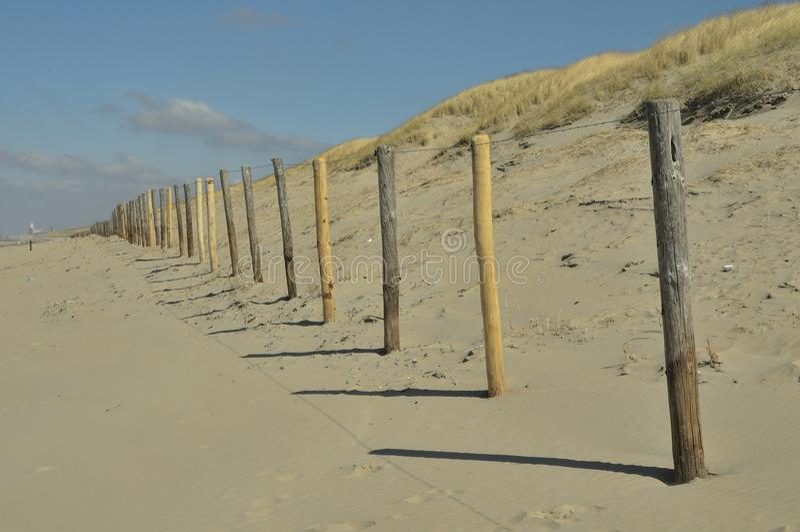 Barrière en bois le long de la plage et des dunes photographie stock libre de droits