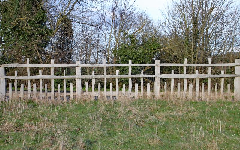 Barrière en bois peu commune avec les rails horizontaux parallèles et les poteaux verticaux de différentes longueurs dans un modè photo libre de droits
