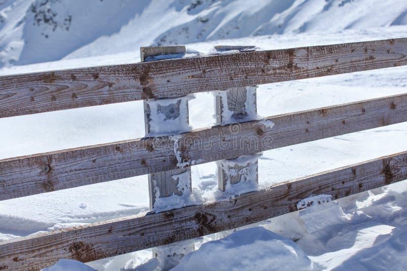 Barrière en bois profondément dans la charge de chute de neige importante un jour ensoleillé lumineux photos libres de droits