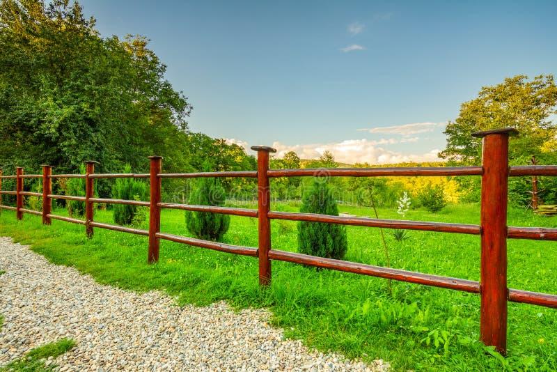 Barrière en bois rouge de jardin et herbe verte photos libres de droits