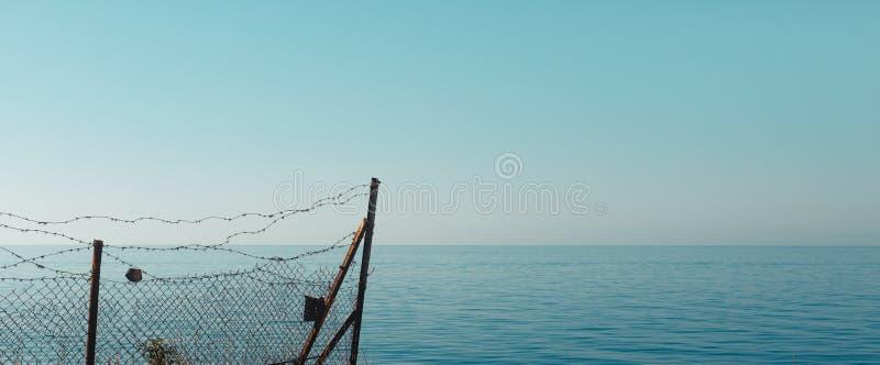 Barrière et barbelé dans la perspective de la mer, du ciel et de l'horizon Le concept de la liberté, de l'indépendance et de la c photographie stock libre de droits