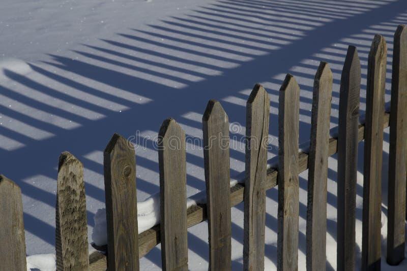 Barrière et ombre en bois sur la neige images stock