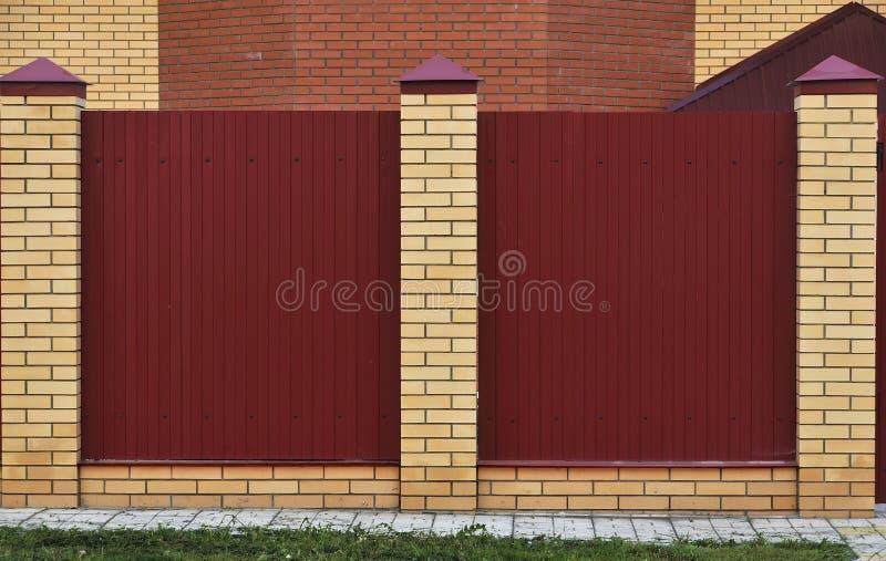 Barrière faite de briques et métal décoratif Barrière rouge avec les éléments jaunes Cl?ture ?lev?e et belle photo stock