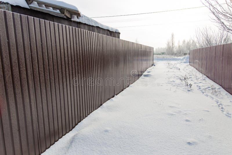 Barrière faite de métal dans la neige en hiver image libre de droits