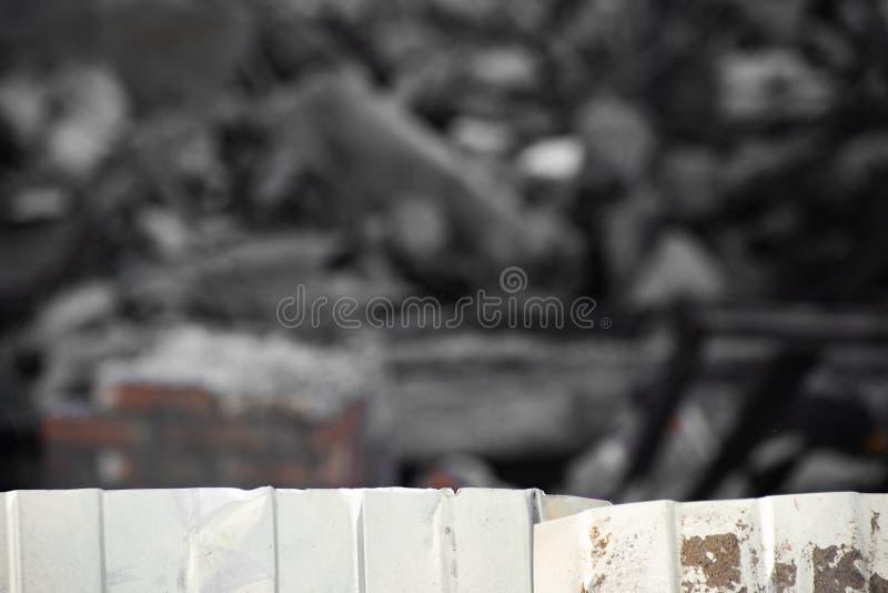 Barrière ondulée en métal sur le fond du bâtiment démantelé photographie stock libre de droits