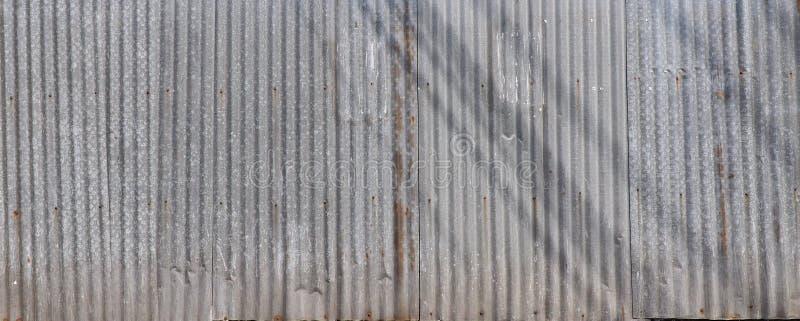 Barrière ondulée grunge de zinc avec des ombres là-dessus images stock