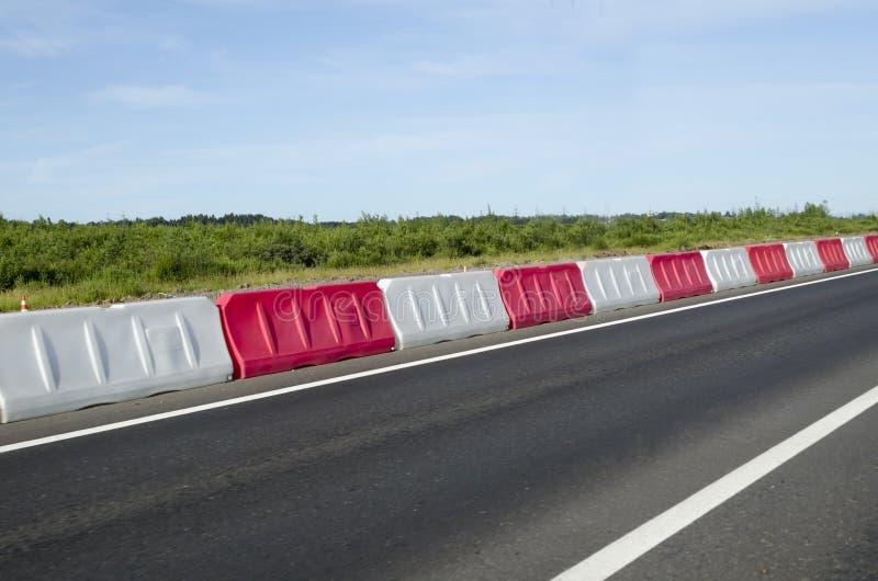 Barrières rouges et blanches en plastique sur la route sur la route, sur la rocade dans la ville moderne signes de bord de la rou image stock