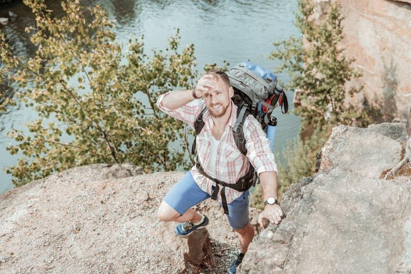 Barrido barbudo del backpacker sudado en su frente que siente cansada mientras que camina fotografía de archivo libre de regalías