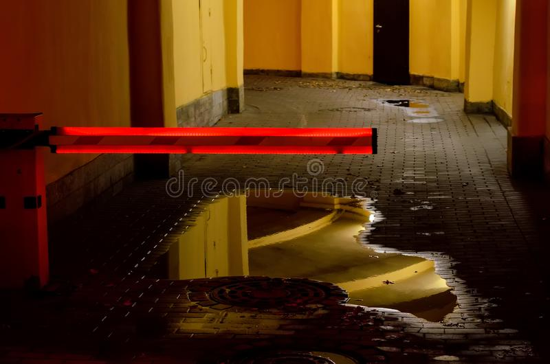 The barrier with red neon light closes the entrance in the parking house. The barrier with red neon light closes the entrance in the parking house in the royalty free stock photography