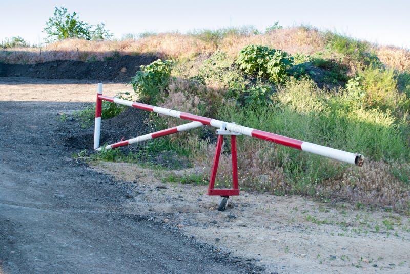 Barriera del metallo di colore rosso e bianco, proibizione del viaggio sulla strada, contro lo sfondo di un percorso degli alberi fotografia stock