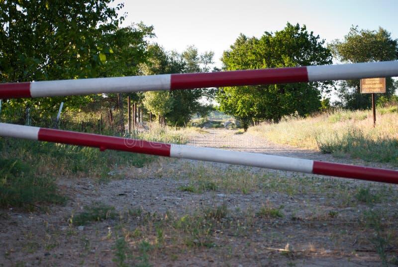Barriera del metallo di colore rosso e bianco, proibizione del viaggio sulla strada, contro lo sfondo di un percorso degli alberi immagini stock libere da diritti