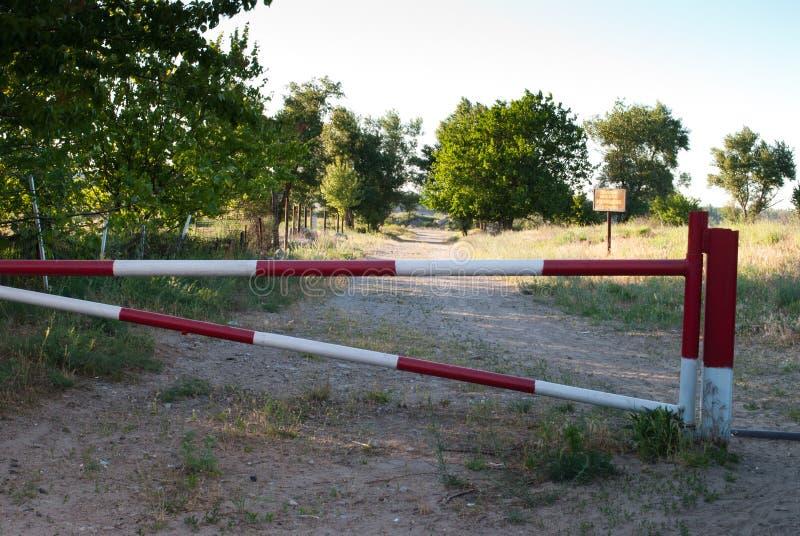 Barriera del metallo di colore rosso e bianco, proibizione del viaggio sulla strada, contro lo sfondo di un percorso degli alberi immagine stock libera da diritti