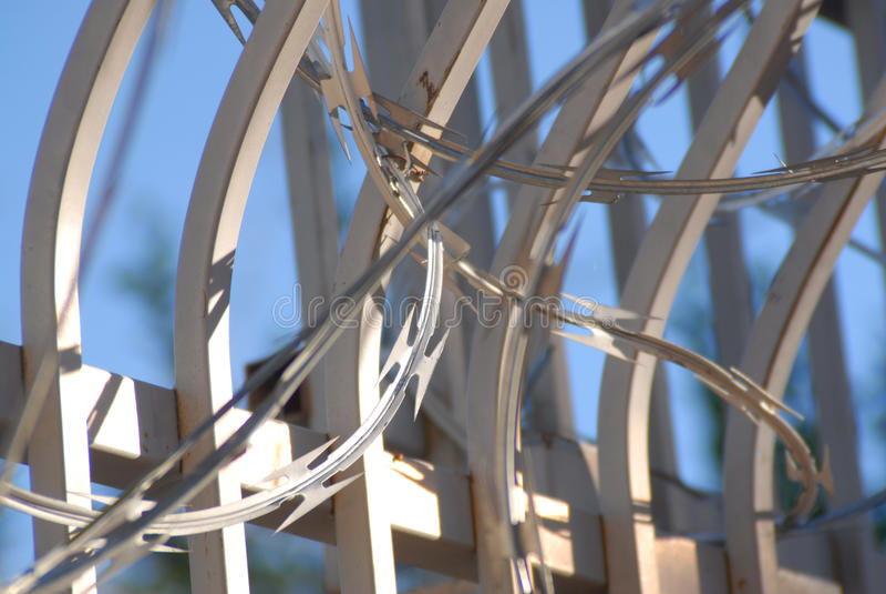 Barriera di sicurezza con il upclose del cielo blu del cavo del rasoio fotografia stock libera da diritti