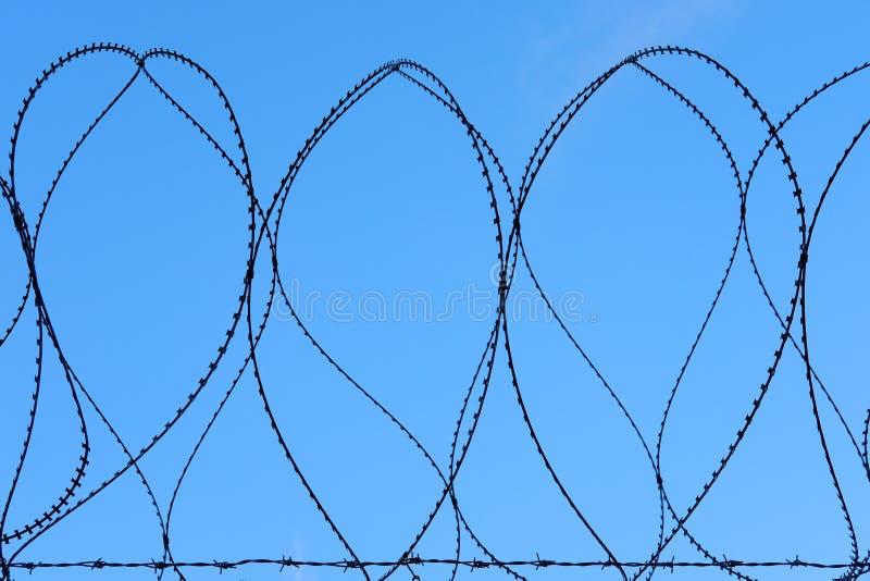Barriera di sicurezza militare Against Blue Sky del cavo pungente del rasoio fotografie stock