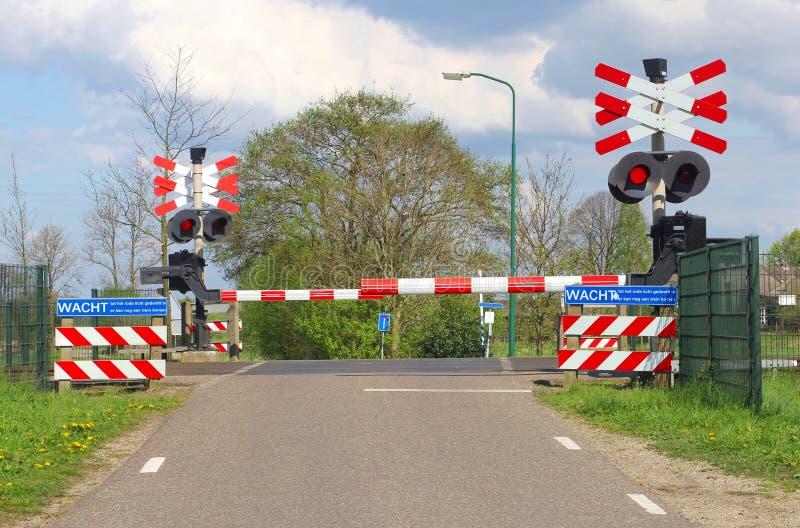 Barriere chiuse della ferrovia ad un passaggio a livello nel ploder, Paesi Bassi immagini stock