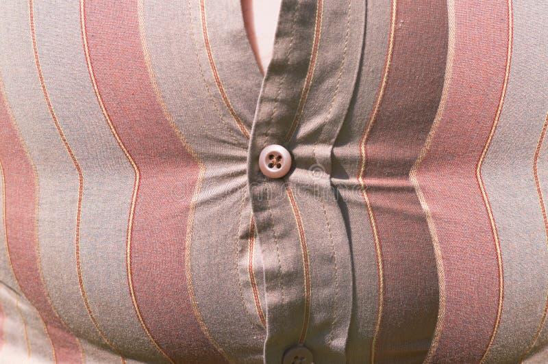 Barriga apertada do excesso de peso da tecla de camisa imagens de stock royalty free