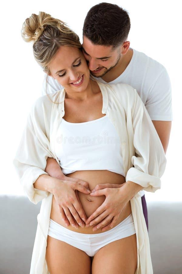 Barriga considerável da terra arrendada do homem novo de sua esposa grávida que faz o coração junto em casa imagem de stock