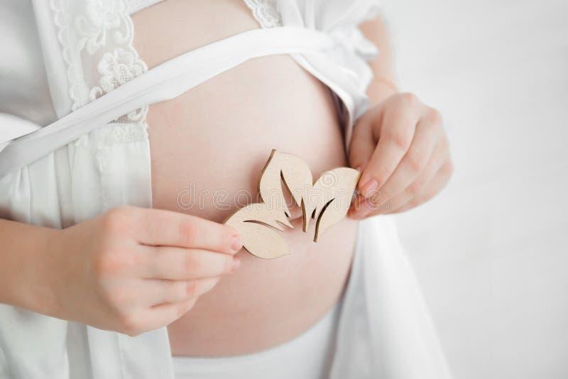 Barriga da gravidez A mamã mantém uma flor cortada da árvore em seu ha fotos de stock royalty free