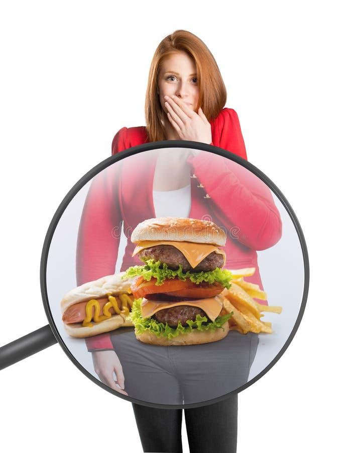 A barriga da mulher com alimento sob uma lupa imagens de stock