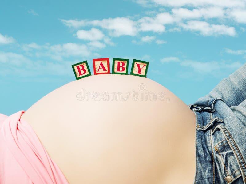 Barriga da mulher grávida com blocos de um brinquedo imagem de stock