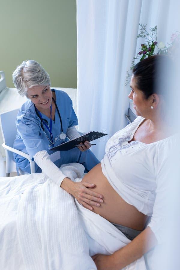 A barriga da mulher gravida de exame do doutor fêmea na divisão imagem de stock