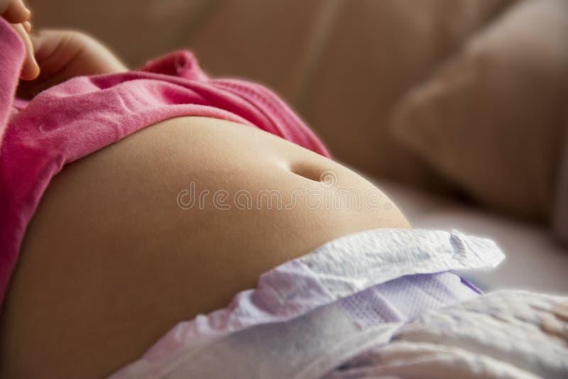 Barriga, barriga de um fim pequeno da criança acima da foto pele nova com um umbigo visível imagens de stock