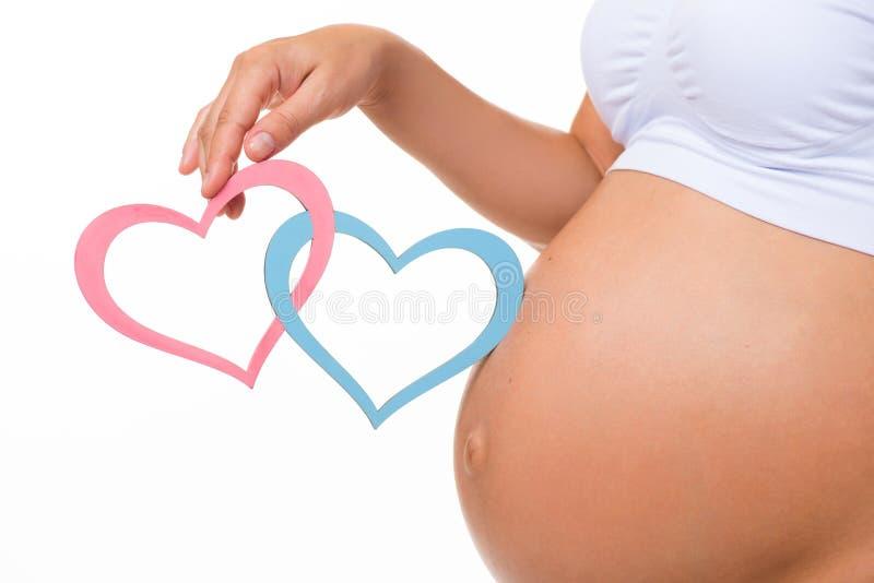 Barriga grávida com coração azul e cor-de-rosa close up horizontal fotografia de stock royalty free