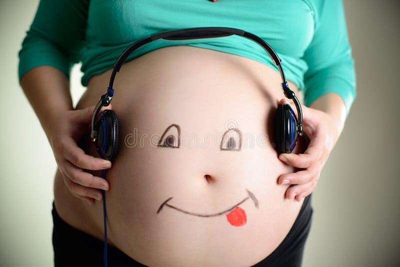 A barriga grávida escuta a música através dos fones de ouvido imagens de stock royalty free