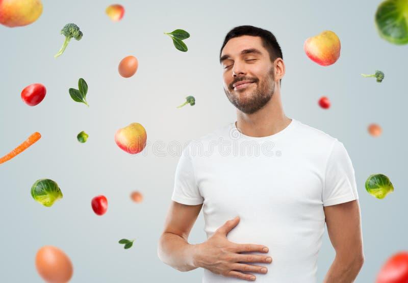 A barriga tocante do homem completo feliz sobre a queda frutifica imagens de stock