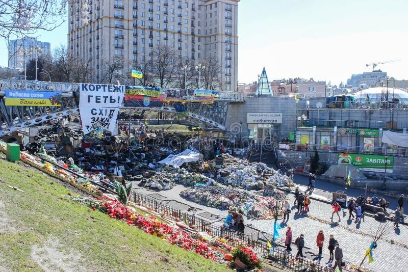 Barrikader av gummihjul och avskr?de, en bro med affischer, flaggor och slogan, m?nga lade blommor p? Maidanen royaltyfri bild