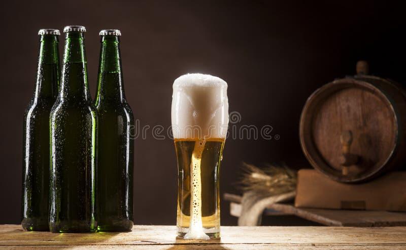 Barril de cerveza con tres botellas y tazas en fondo marrón imágenes de archivo libres de regalías