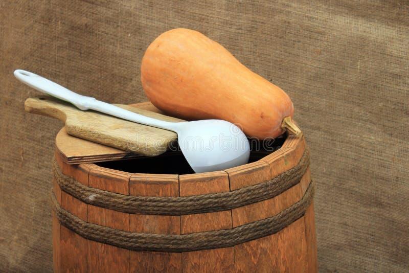 Barril de madera con la cucharón y la calabaza en fondo de la arpillera imagenes de archivo
