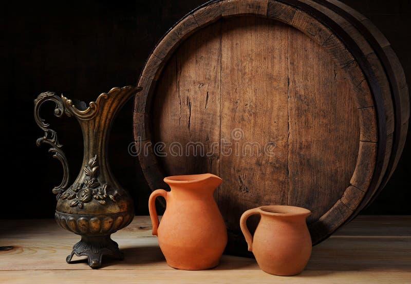 Barril de madera, el jarro del metal y loza de barro fotografía de archivo libre de regalías