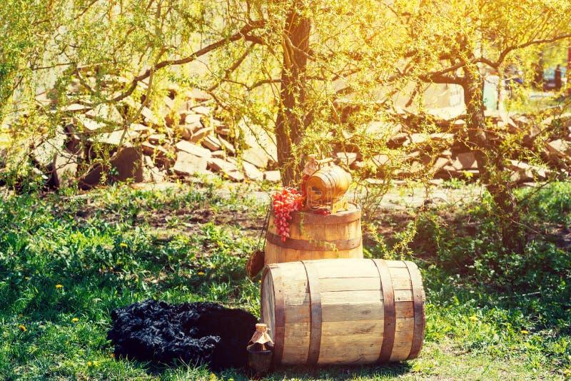 Barril de vino de madera viejo con la botella de vino y de uvas en ella imagenes de archivo