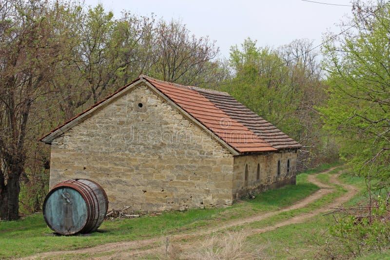 Barril grande viejo delante de la casa de piedra antigua imagenes de archivo