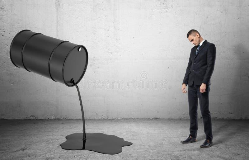 Barril inclinado con el aceite líquido negro que vierte fuera de él encendido y de hombre de negocios triste dissapointed fotografía de archivo libre de regalías
