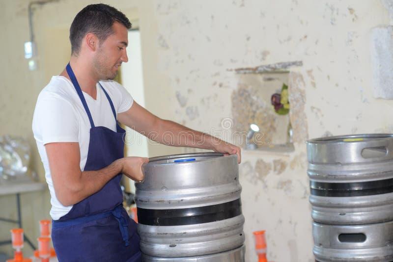 Barril que lleva del trabajador con la cerveza en la cervecería imagen de archivo libre de regalías
