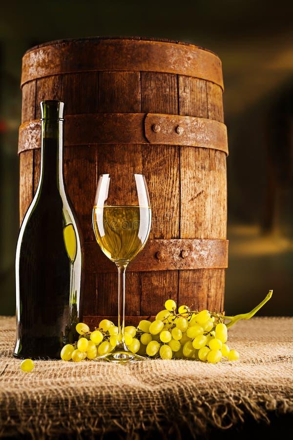 Barril viejo de la composición de la vid con la botella y el winegrape de la copa imagenes de archivo