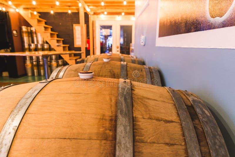 Barriles de madera en una casa o una cervecería artesanal del golpecito fotos de archivo